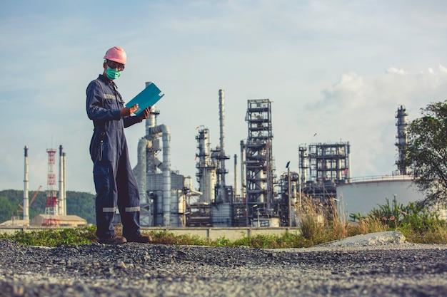Männliche arbeiter kontrollieren und dokumentieren die prozessraffinerie auf der industriebaustelle öl und gas.