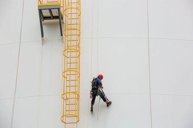 Männliche arbeiter kontrollieren unter seil-abseil-höhe tank seilzugangsinspektion der dicken-panzerplatten-speichertank-sicherheitsarbeit in der höhe.