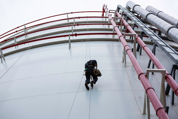 Männliche arbeiter kontrollieren unter seil nach unten höhe tank in der nähe von pipeline seilzugangsinspektion der dicken-panzerplatten-speichertank-sicherheitsarbeit in der höhe.