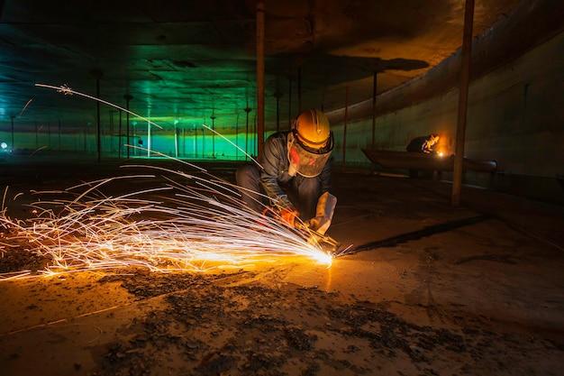 Männliche arbeiter metallschneidfunken auf der stahlplatte des tankbodens mit blitzlicht, nahaufnahme, schutzhandschuhe und maske in seitlich begrenztem raum tragen.
