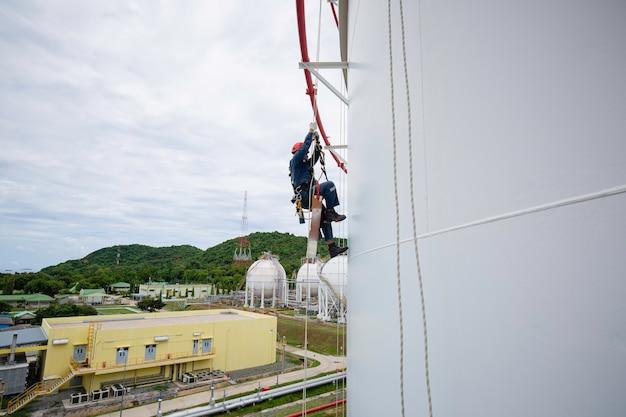 Männliche arbeiter mit seilzugang industriearbeiten in der höhe tanköl-tragegurt, helmsicherheitsausrüstung seilzugangsinspektion von dicken tanköl- und gas-hintergrundkugelförmigen propantanks.
