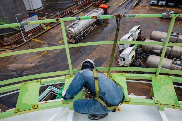 Männliche arbeiter mit sicherheitsgurt und sicherheitsleine, die am hohen handlauf auf dem dachtankchemikalie arbeiten.