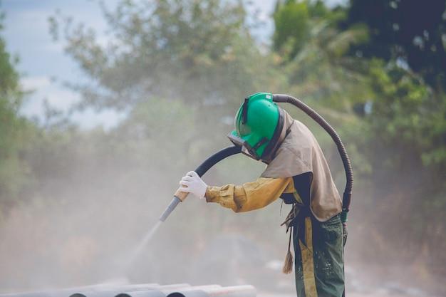 Männliche arbeiter sandstrahlen staubprozess reinigung der rohrleitungsoberfläche auf stahl vor dem lackieren in der fabrik.