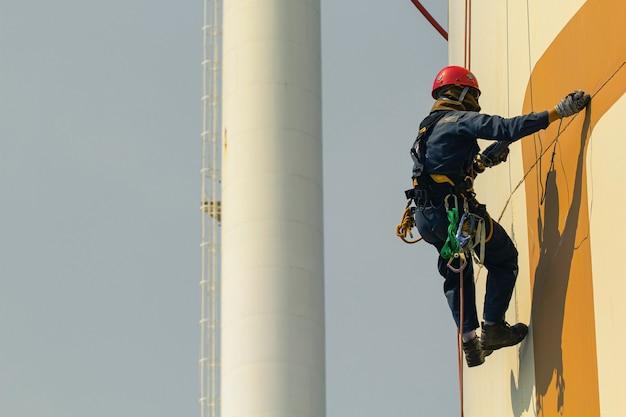 Männliche arbeiter seilzugangshöhe sicherheitsinspektion der dickenlageröl- und gastankindustrie