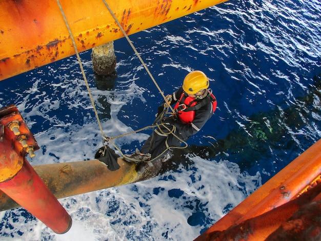 Männliche arbeiter seilzugangsinspektion der dicken offshore-bohrer gelbe öl- und gasproduktions-erdölpipeline.