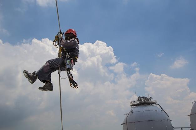 Männliche arbeiter seilzugangskontrolle der dicke lagertank industrie hintergrund blauer himmel