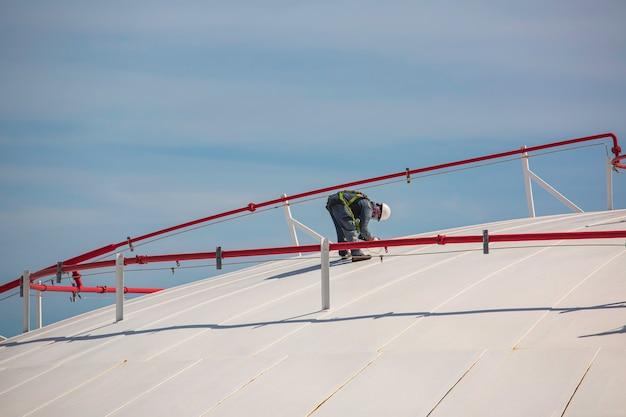 Männliche arbeiter sind für die inspektion der ultraschalldicke der dachplattenkuppel oben des lagertanks.