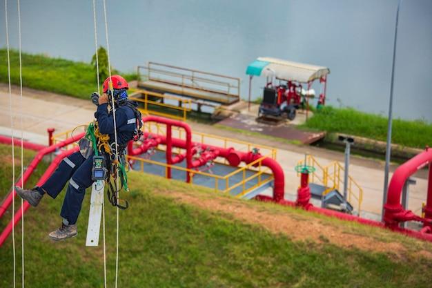 Männliche arbeiter von oben kontrollieren den seilzugang des tanks mit seilzugangsinspektion der dickenmantelplatte des lagertanks gassicherheitsarbeiten in der höhe.