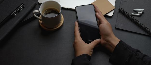 Männliche arbeiterhände, die smartphone auf dunklem modernem büroschreibtisch halten