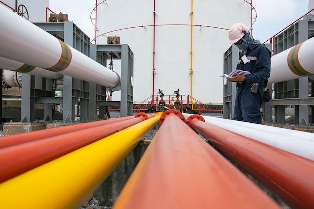 Männliche arbeiterinspektion am flanschrohr der sichtprüfungsprotokollpipeline der öl- und gasindustrie