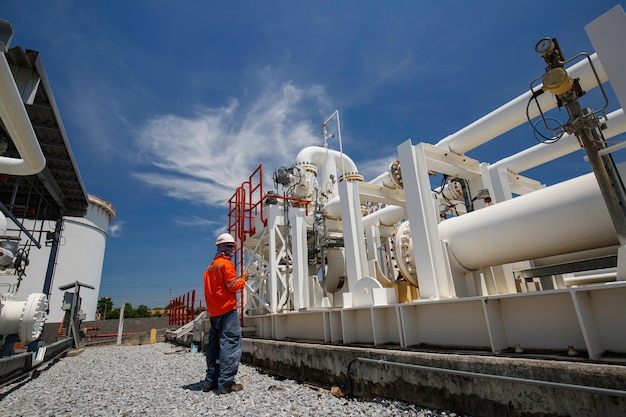 Männliche arbeiterinspektion an langen stahlrohren und rohrkrümmern in der stationsölfabrik während des raffinerieventils der sichtprüfungsaufzeichnung Premium Fotos