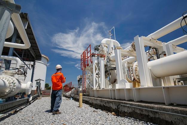 Männliche arbeiterinspektion an langen stahlrohren und rohrkrümmern in der stationsölfabrik während des raffinerieventils der sichtprüfungsaufzeichnung
