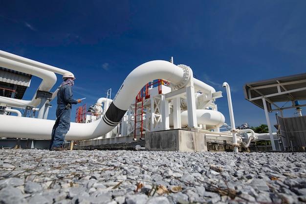 Männliche arbeiterinspektion an langen stahlrohren und rohrkrümmern in der stationsölfabrik während des raffinerieventils der visuellen kontrollaufzeichnung der pipeline-öl- und gasindustrie