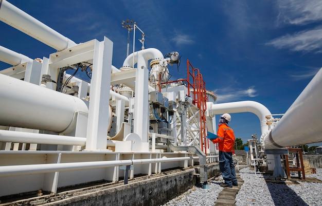 Männliche arbeiterinspektion an langen stahlrohren und rohrkrümmern in der stationsölfabrik während des raffinerieventils der visuellen kontrollaufzeichnung der pipeline-öl- und gasindustrie Premium Fotos