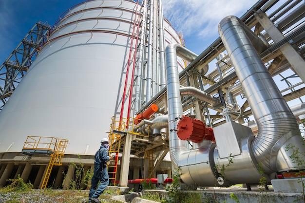 Männliche arbeiterinspektion an langen stahlrohren und rohrkrümmern in der stationsölfabrik während des raffinerieventils des tanks für die visuelle überprüfung