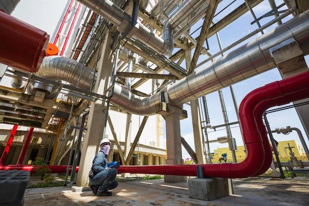 Männliche arbeiterinspektion an langen stahlrohren und rohrkrümmern in der stationsölfabrik während des raffinerieventils des visuellen prüfprotokolls