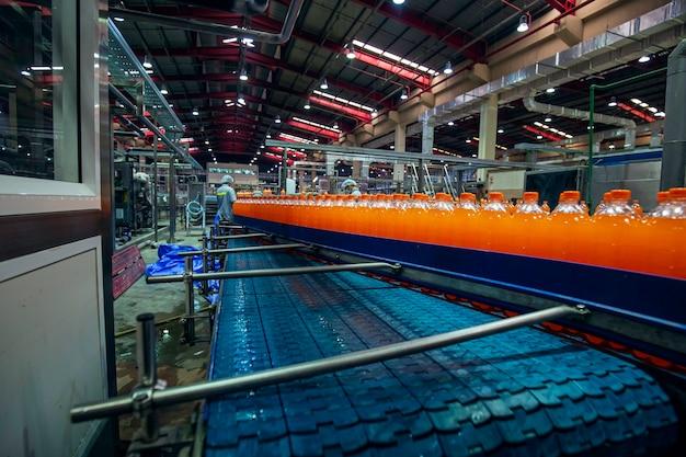 Männliche arbeiterinspektion innenraum der getränkefabrik. förderer, der mit flaschen für saft oder wasser fließt.