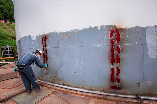 Männliche arbeiterinspektion spay farbe spuckte rote schweißhülle plattenklebrigkeit durch eindringprüfung gefunden.