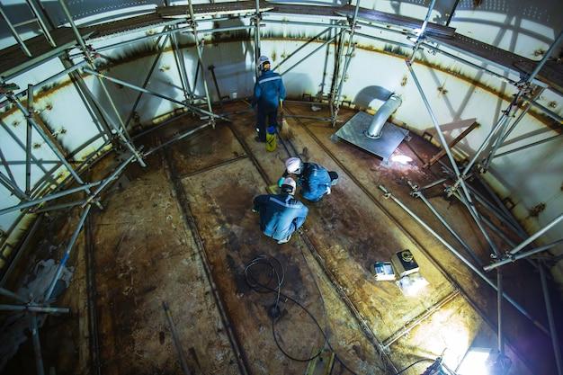 Männliche arbeiterinspektion vakuumtest bodenplatte tank löschwassertank gerüst fortschritt schweißleck interne begrenzte spezifikation