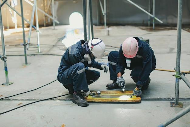 Männliche arbeiterinspektion vakuumtest bodenplatte tank petrochemischer stahl schweißleckage interne begrenzte spezifikation