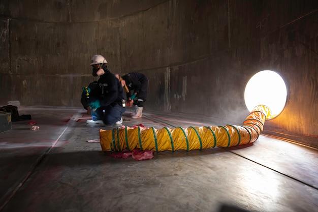 Männliche arbeiterinspektion visuelle chemikalien edelstahlgebläse frischluft in lagertank beengten raum