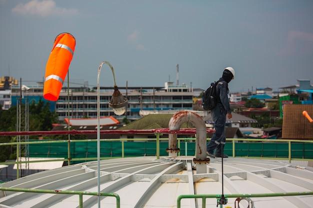 Männliche arbeiterinspektion visuelles dachlagertanköl windsackanzeige des windes auf dem chemischen konus des tanks.