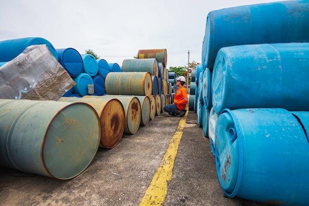 Männliche arbeiterinspektion zeichnet alte fassöl-lagerfässer blau und grün horizontal oder chemisch für die industrie auf. Premium Fotos