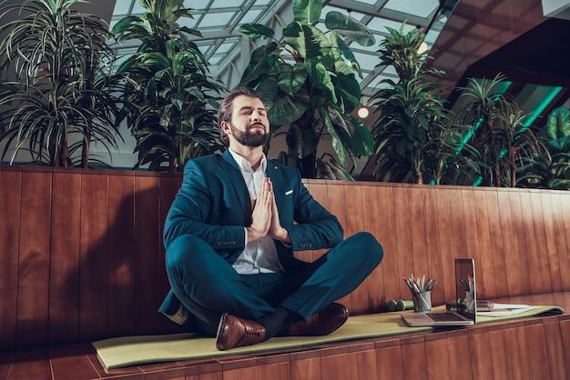 Männliche arbeitskraft, die auf bank im büro meditiert.