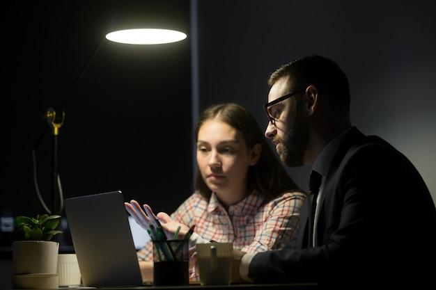 Männliche arbeitskraft, die marketingpläne weiblichem mitarbeiter erklärt