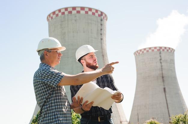 Männliche architekten, die zusammen dokumente an der elektrischen energie wiederholen