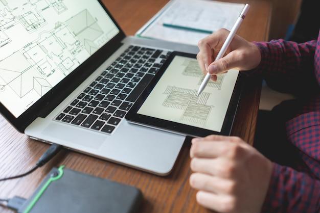Männliche architektenarbeit mit computer auf holztisch