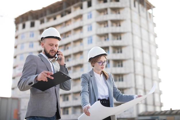 Männliche architektur, die auf dem mobiltelefon steht nahe der weiblichen architektur hält plan an der baustelle spricht