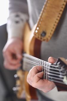 Männliche arme, die e-gitarre der klassischen form spielen