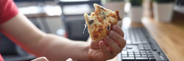 Männliche arme, die großes stück knusprige frische pizza nehmen
