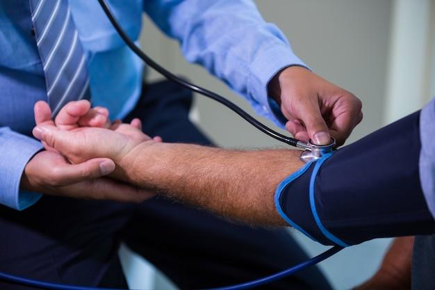 Männliche arzt den blutdruck des patienten überprüft