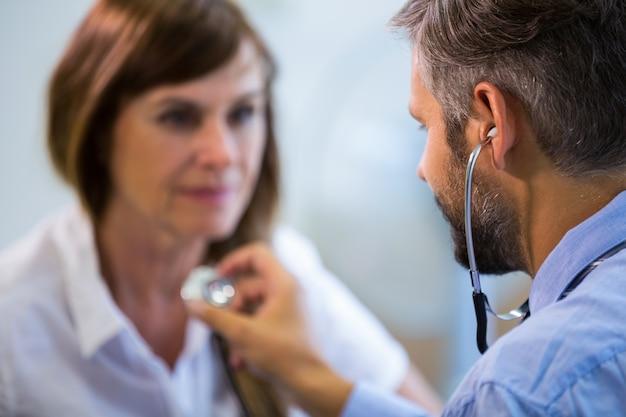 Männliche arzt einen patienten untersucht