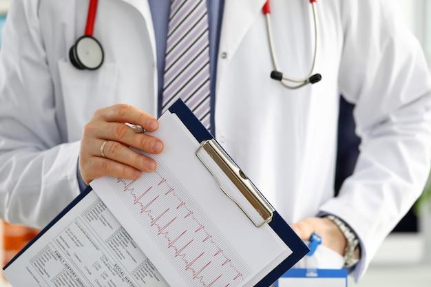 Männliche arzthand halten silbernen stift, der patientenverlaufsliste am klemmblock füllt. körperliche untersuchung krankheitsprävention station runde besuch check 911 verschreiben heilmittel gesunden lebensstil konzept