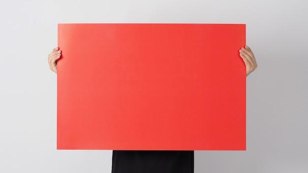 Männliche asiatische hand hält das leere rote farbpapier