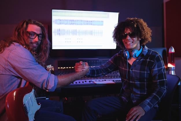 Männliche audioingenieure, die digitales tablet verwenden