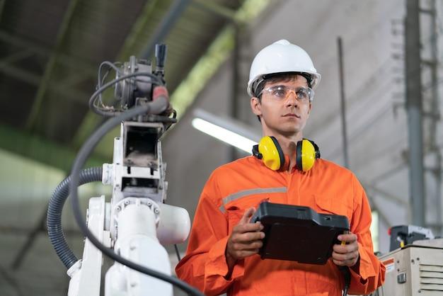 Männliche automatisierungsingenieure tragen eine orangefarbene uniform mit helmsicherheit, die eine roboterarmschweißmaschine mit einer remote-systemplatine in einer industriefabrik steuert. konzept der künstlichen intelligenz.