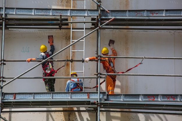 Männliche bauarbeiter tanken öl, das gerüste auf der raffinerie vor ort installiert