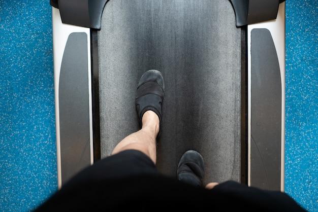Männliche beine, die auf tretmühle in der turnhalle gehen und laufen. cardio-training ausüben