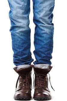 Männliche beine in jeans und lederstiefeln