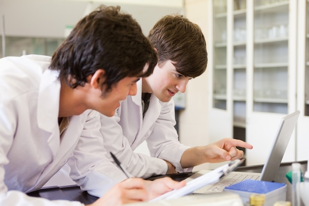 Männliche chemiestudenten, die einen bericht schreiben