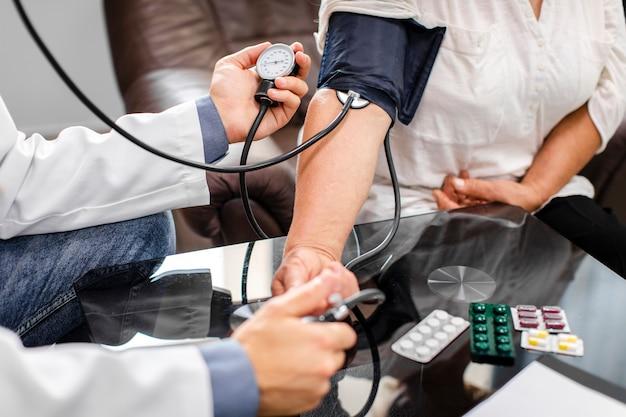 Männliche doktorhände, die spannung zu einem patienten messen