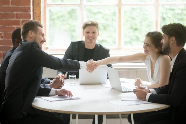 Männliche exekutive, die hände mit weiblichem mitarbeiter, teamworkeinführung rüttelt.