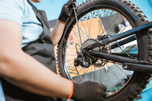 Männliche fahrradmechaniker hände in handschuhen, die eine kette befestigen