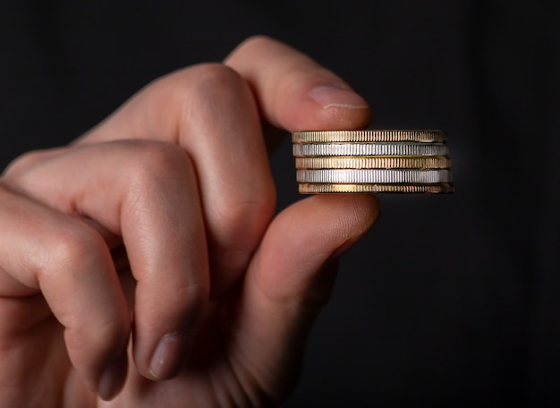Männliche finger, die stapel von münzen halten. konzept der geldwäsche, schwarze falsche buchhaltung.