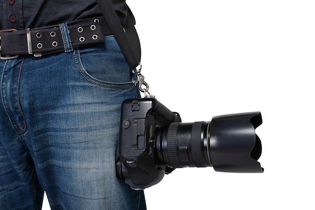 Männliche fotografenbeine mit gürtel, der digitalkamera mit professionellem objektiv hält. fotogeschäftskonzept