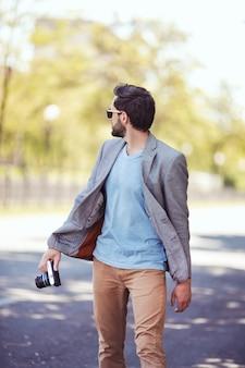 Männliche fotografenfront, die draußen auf der stadtstraße geht